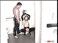 Latex-clad cuffed Nicole Marciano gets her sexy body drenched in man's pee in the toilet room