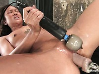 Oriental Jandi Lin has her clit vibrated and her hole drilled by power dildo from behind