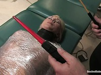 Wrapped up helpless blonde Samantha Sin with bar cuffs on her ankles gets caned