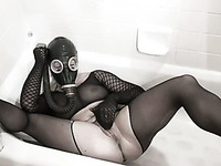 Babe in fishnet outfit and respirator is pissing lying in the bath tube