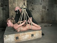 Nude slave girl Holly Wellin gets tied by master in black uniform and mask