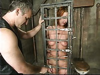 Redhead Ivy Red gets water tortured in cage by Torque before suspension bondage