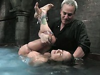Tattooed naked slave girl Nadia Styles gets dunked in huge water tank in the middle of the dungeon