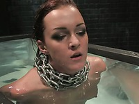 Nude Sara Faye with cuffed hands behind her back finds herself in a huge water tank