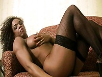Black muscle woman Alexis Ellis in black stockings and red lingerie bares her round boobs