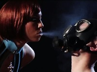Latex domina Stella Van Gent smokes a cigarette in front of her motionless slave man in gas mask