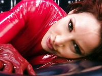 Well-stacked Bianca Beauchamp dressed in red latex shows off her body lines in black rubber room