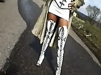 Stella Van Gent in sexy high boots and long fur coat walking the rod in the afternoon