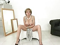Well-endowed mature lady Lady Sonia poses in long dress and high heel shoes