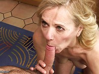 Fully nude aged blonde Lili gives blowjob to young guy on her knees in the middle of the room