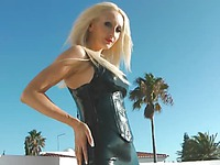 Tall leggy blonde Saffron Taylor in latex mini dress and high heel boots poses rooftop