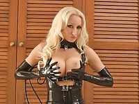 Blonde haired english fetish model Saffron Taylor poses in tight black suit made of latex