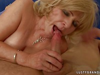 Aged blonde haired woman Sally G. in black thong gives oral pleasure to young guy on the bed