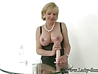 Sexy bodied mature blonde Lady Sonia takes dildo between her huge boobs