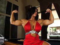 Female bodybuilder Angela Salvagno wearing a red dress shows off her muscles