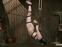 Juliette March is gagged and tied with chains to the wall, with a sex machine fucking her pussy.