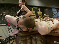 Wicked bitch Gia DiMarco uses all her strenght to fuck a tied up stud bent over a table with a toy.