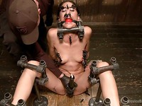 Lyla Storm posing before her bondage master puts her into kinky contraptions and pegs.