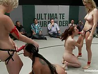 Iona Grace on her knees in front of kinky fetishists getting fed with a strap-on in cat fights.